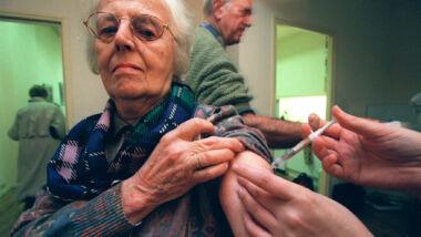 Een vrouw wordt donderdag bij een Amsterdamse huisarts gevaccineerd tegen griep.