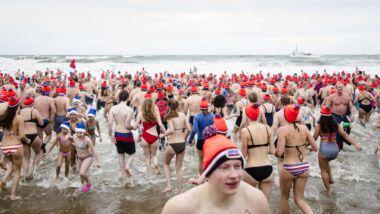 Mensen rennen met unox mutsen de zee in op nieuwjaarsdag