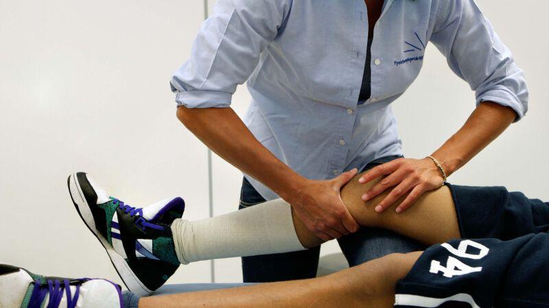 Fysiotherapeut helpt een jongen aan pijn in zijn knie in 2008