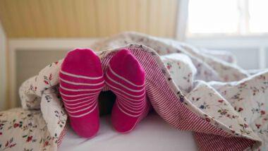 Vrouw ligt met sokken in bed onder een dik dekbed met slaaptekort.