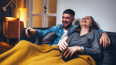 Stel kijkt televisie onder een dekentje op de bank