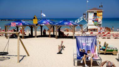 mensen genieten van de zon op het strand in een paarse strandstoel